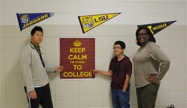Students and principal point to college poster